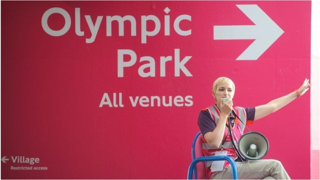 Volunteer directs spectators towards the Olympic Park