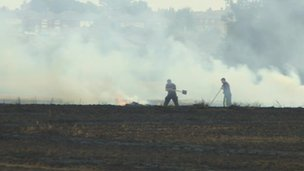 Firefighters damping down in the field