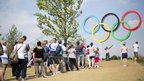 Crowds line up to have their photo taken by the Olympic rings