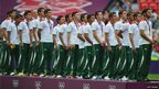 The Mexican football team listens to the anthem at the medal ceremony