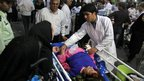 An Iranian medic attends to an injured woman as people gather outside a hospital in the town of Ahar, some 60km (40 miles) east of Tabriz, after a strong earthquake hit northwestern Iran on Saturday