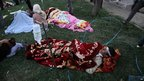 Injured Iranians lie on the grass outside a hospital in the town of Ahar, some 60km (40 miles) east of Tabriz, after a strong earthquake hit northwestern Iran on Saturday.