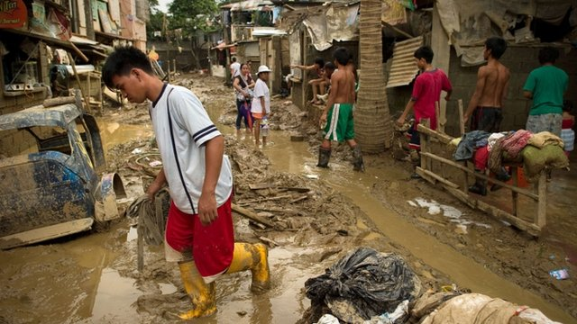 Local residents return to their homes and start to clean up the mud left after the floods in San Mateo town, Rizal province east of Manila.