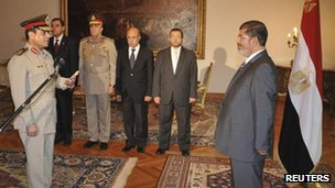 Egypt's President Mohammed Morsi (R) observes as new Defence Minister Abdel-Fattah al-Sisi receives his orders at the presidential palace in Cairo on Sunday