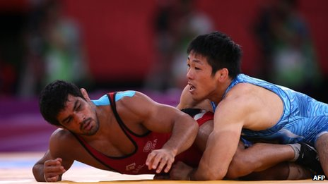 """India's Sushil Kumar (L) wrestles Japan""""s Tatsuhiro Yonemitsu in their Men""""s 66kg Freestyle gold medal match on August 12, 2012 during the wrestling event of the London 2012 Olympic Games"""