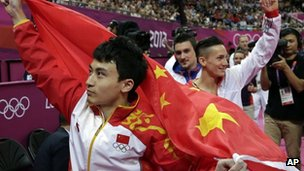Chinese gold medallist Feng Zhe celebrates holding his national flag on 7 August 2012