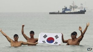 Swimmers holding South Korea&#039;s flag in the port city of Uljin