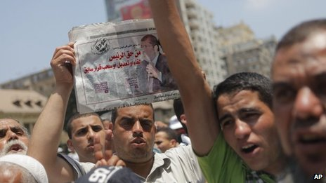 "Supporters of Mohammed Mursi hold up a newspaper whose headline reads: ""The president has the right to cancel, change or dissolve an old decision"" (10 July 2012)"