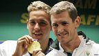 South Africas London 2012 Olympic games gold medalist swimmers, Cameron van der Burgh (R) and Chad le Clos show off their medals as they are welcomed by fans at the O.R Tambo International Airport in Johannesburg