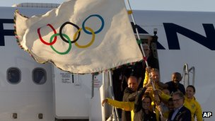 Rio de Janeiro's Mayor Eduardo Paes, top left, Carlos Arthur Nuzman, President of the Brazilian Olympic Committee, bottom right, and Brazilian athletes hold the Olympic flag on its arrival in Rio de Janeiro, Brazil