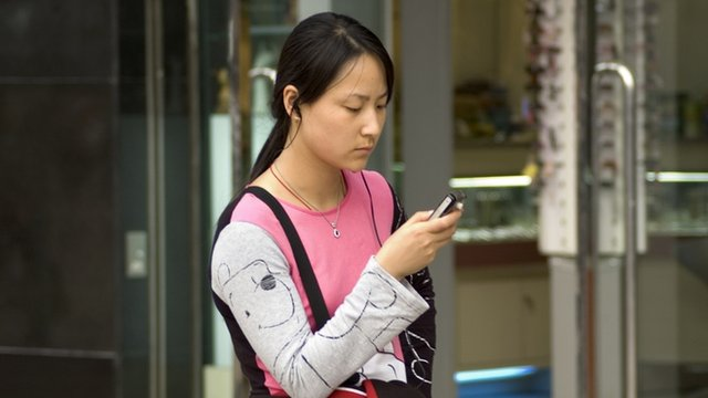 Girl using mobile phone in Wangfujing, Beijing
