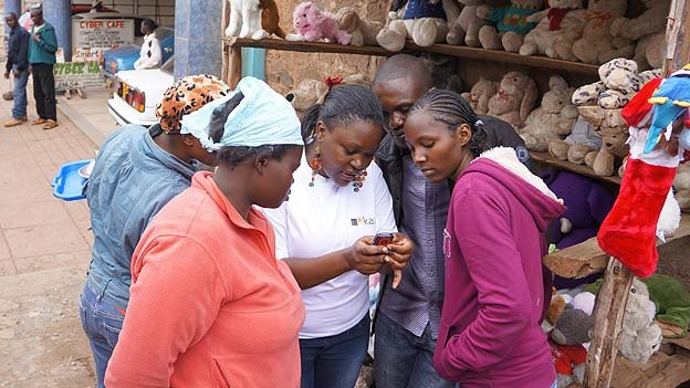 A group of Kenyans watch a demonstration of the M-Kazi job-hunting service