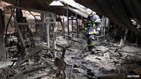 French firemen inspect damage inside a leisure centre on Tuesday after overnight clashes in Amiens, northern France