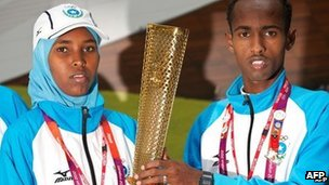 Somali athletes Mohamed Hassan Mohamed (R) and Zamzam Mohamed Farah pose for pictures with a London 2012 Olympic Torch during a visit to to the Foreign and Commonwealth Office in London, on 10 August 2012