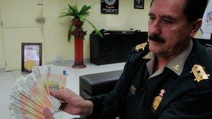 Peru police chief Cesar Cortijo holds up fake bills