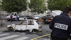 French policemen remove cars destroyed in overnight clashes with gangs of youths in Amiens