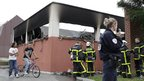 Youths walk near French firemen and police outside a leisure centre hours after overnight clashes in Amiens
