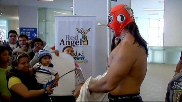 A Mexican wrestler talking to fans