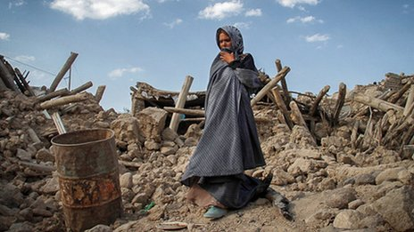 A survivor of the Iranian quakes stands near the ruins of damaged houses in Azerbaijan province (image from 13 August 2012)