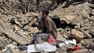 A victim of Saturday's earthquake grieves as he sits on ruins of buildings in a village near the city of Varzaqan, Iran 13 August 2012