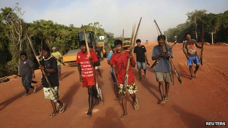 Brazilian indigenous walk past heavy machinery