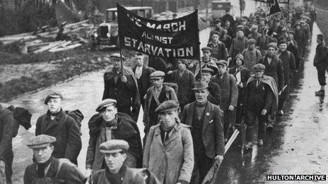 Unemployed men on a hunger march pass through a British town, circa 1935.