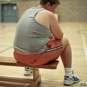 An overweight boy sits on a gym bench