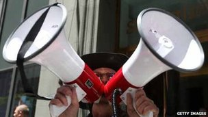 Man shouting into two megaphones