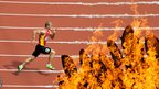 A runner goes past the Olympic flame