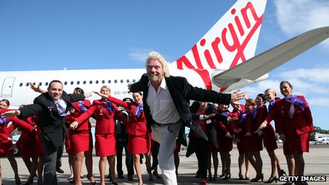 Richard Branson posing with crew by a Virgin aeroplane