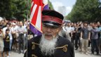 Men dressed as Imperial Japanese Army soldiers march at Yasukuni Shrine in Tokyo
