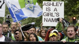 "Rival fans carry a sign that reads ""Ashley is a girl's name"""
