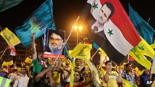 Hezbollah supporters wave Hezbollah and Syrian flags with a picture of Syrian President Bashar Assad, during a rally on 18 July