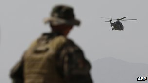 A French Army mentor looks on as a Eurocopter AS 532 Cougar helicopter  flies in Kabul on August 12, 2012
