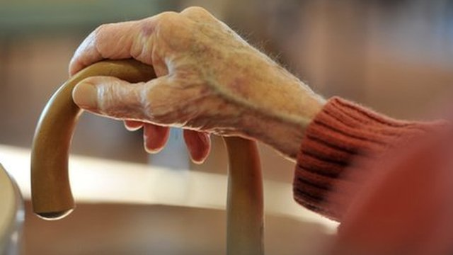 An elderly person's hand holding a walking stick