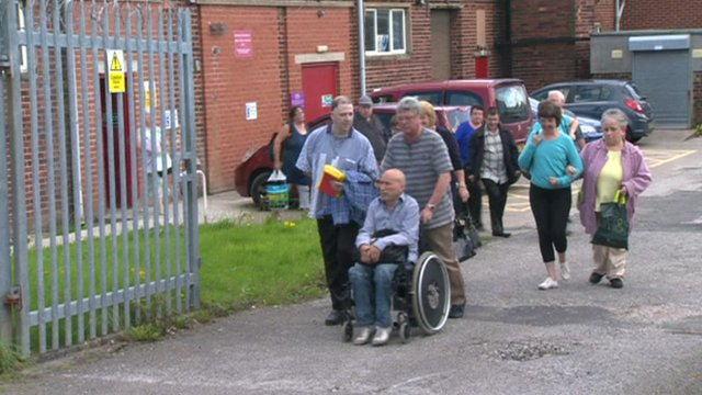 Workers leave the Remploy factory in Wigan for the last time