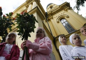Orthodox Christian children hold flowers at St Mary Magdalene's Orthodox Cathedral in Warsaw, 16 August