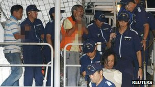 Kyodo photo of Chinese activists arrested at a disputed island in the East China Sea, known as Senkaku in Japan or Diaoyu in China, being escorted by Japan Coast Guard at a port in Naha, Okinawa, on 16 August, 2012