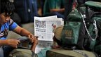 A man from India&#039;s north-eastern states reads a newspaper showing news about people leaving as he waits with others to board a train home, at a railway station in Bangalore, India, Thursday, 16 August, 2012