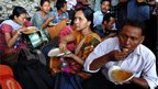 Indian minority north-eastern residents eat while waiting on a train platform as they prepare to leave the city following rumours of communal violence against them, at a railway station in Bangalore on August 16, 2012