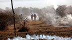 Striking workers are caught in teargas as police open fire on the workers at the Marikana platinum mine in South Africa on 16 August 2012