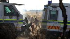 Workers throw stones as police open fire on striking miners at the Marikana platinum mine in South Africa on 16 August