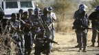 A policeman points at the bodies of shot miners after officers opened fire on striking workers at the Marikana platinum mine in South Africa on 16 August