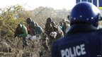 A policeman fires at striking miners at the Marikana platinum mine in South Africa on 16 August
