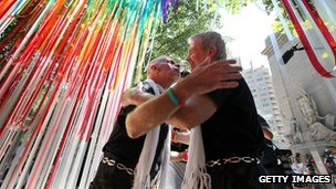 Two men embrace under a rainbow-coloured canopy after being married