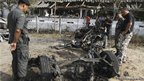 Thai police officers inspect the site of a car bomb attack