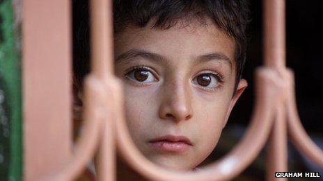 Boy peering through a window in the Kurdish region of north-east Syria
