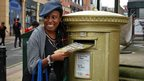 Woman posing next to Jess Ennis' postbox