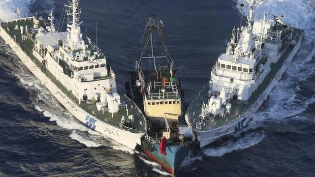 A boat, centre, is surrounded by Japan Cost Guard patrol boats after some activists jumped from the boat on 15 August, 2012