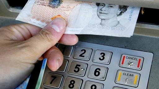 Person taking out a £10 note from a cashpoint